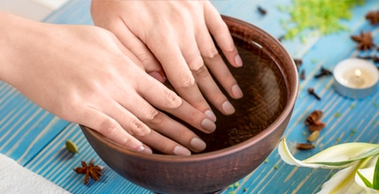 services; woman's manicured hands in water bowl