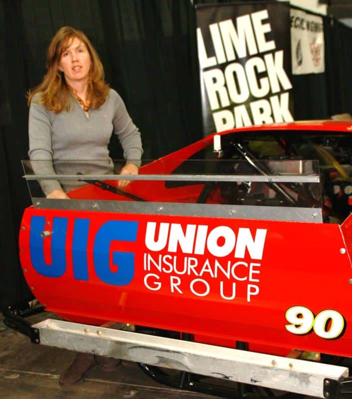 Renee poses with her UNION Insurance Group sponsored car on display in the Lime Rock Park booth.