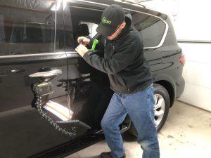 tech performing paintless dent repair