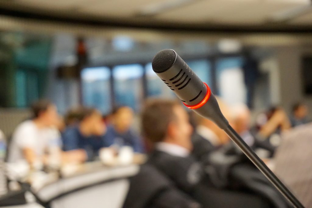 A podium mic against a blurred background of people sitting.
