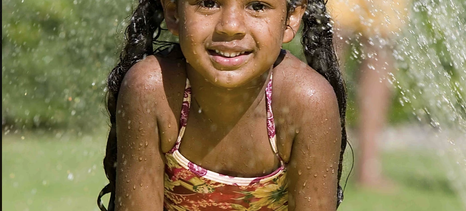 Smiling girl playing on slip and slide