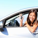 Young woman in driver seat of car showing off keys