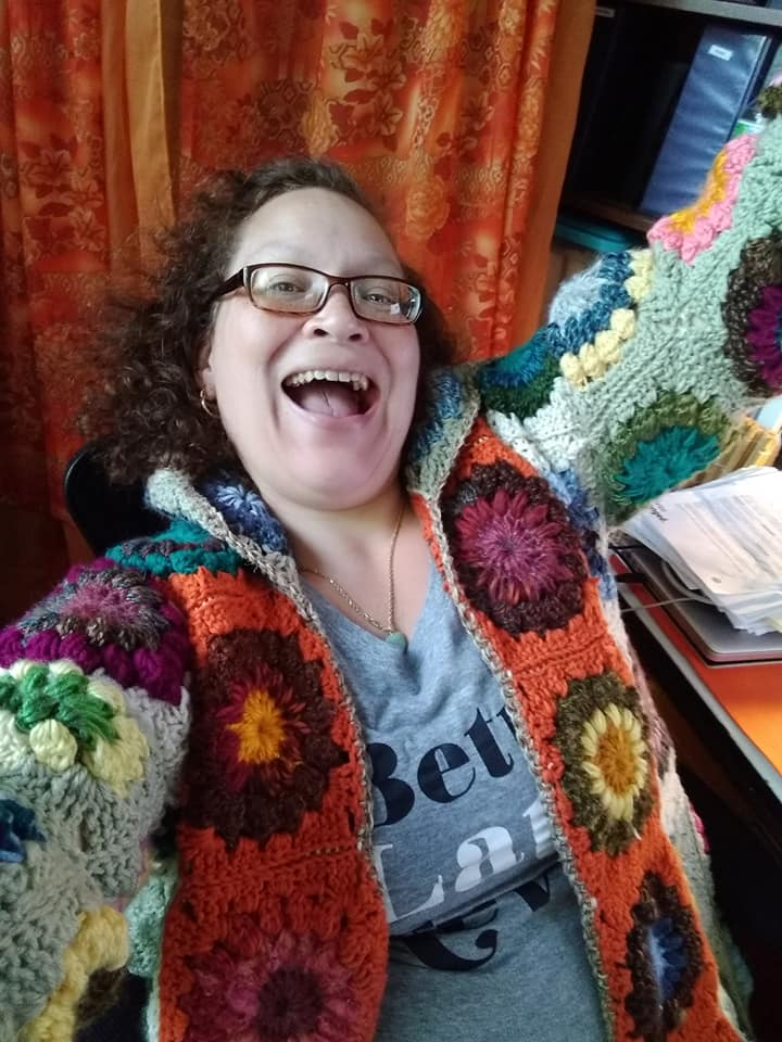 Evangeline is ecstatic you are here, wearing her handmade granny square sweater jacket.