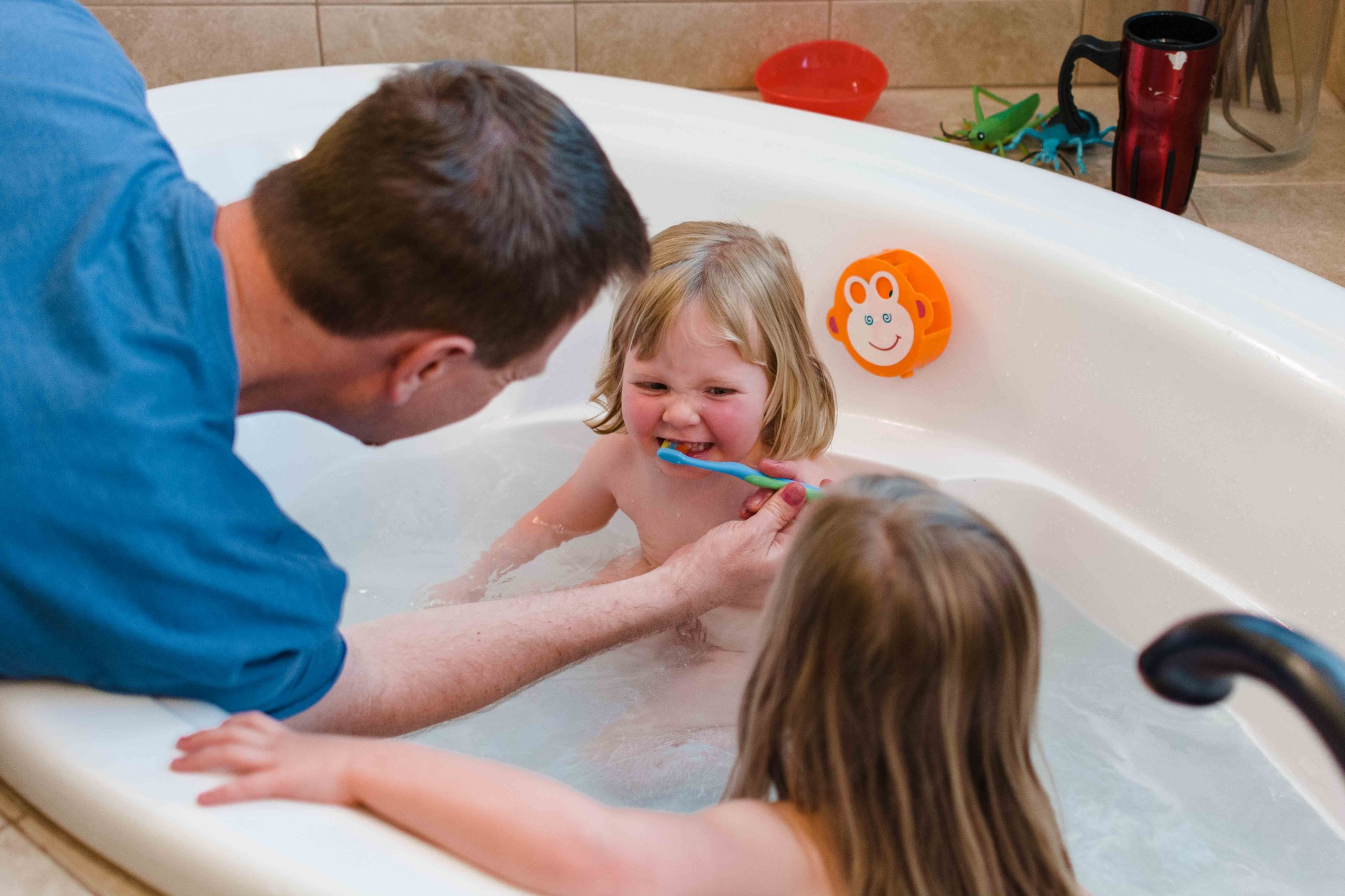 dad brushing teeth of toddlers in bath documentary candid family photography