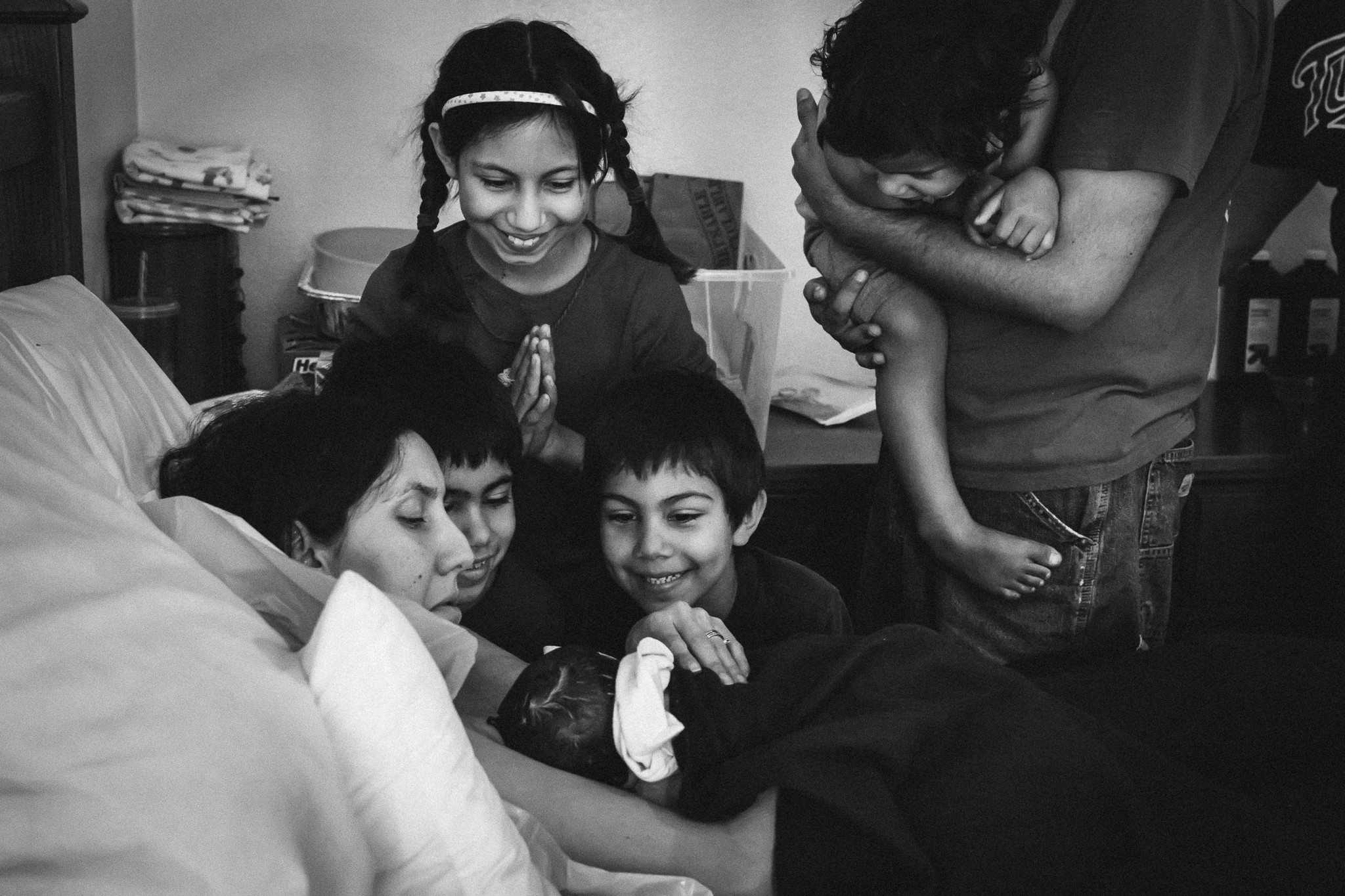 children looking at newborn baby girl documentary birth photography