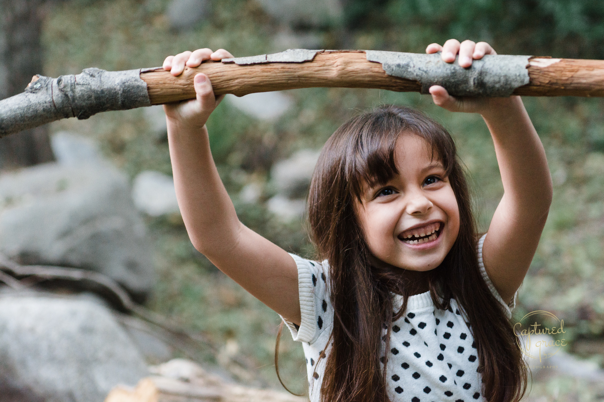 girl playing with stick documentary family photography