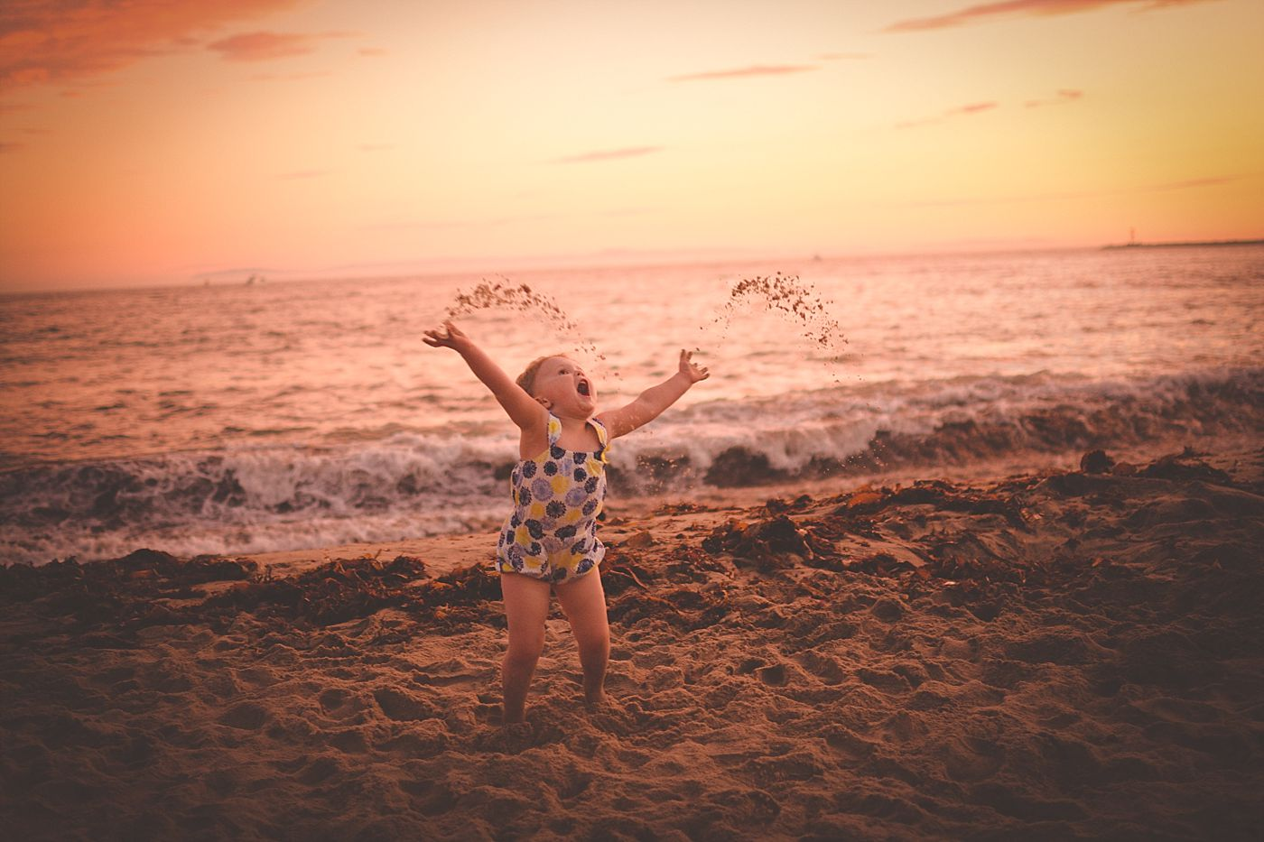 toddler throwing sand at corona del mar, captured grace by erin documentary family photography