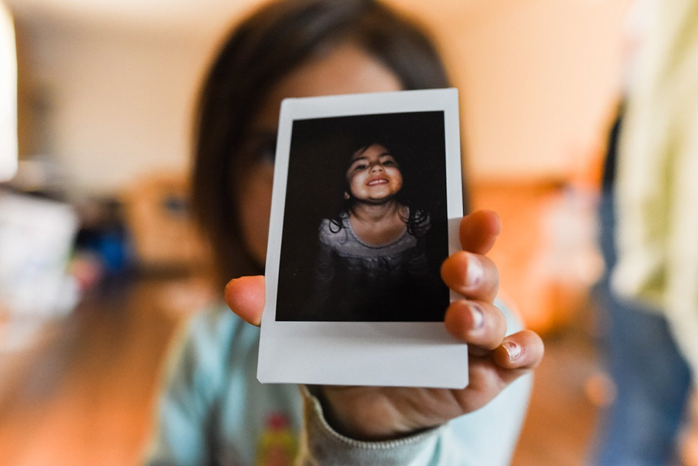 toddler showing off polaroid of self redlands family photographer