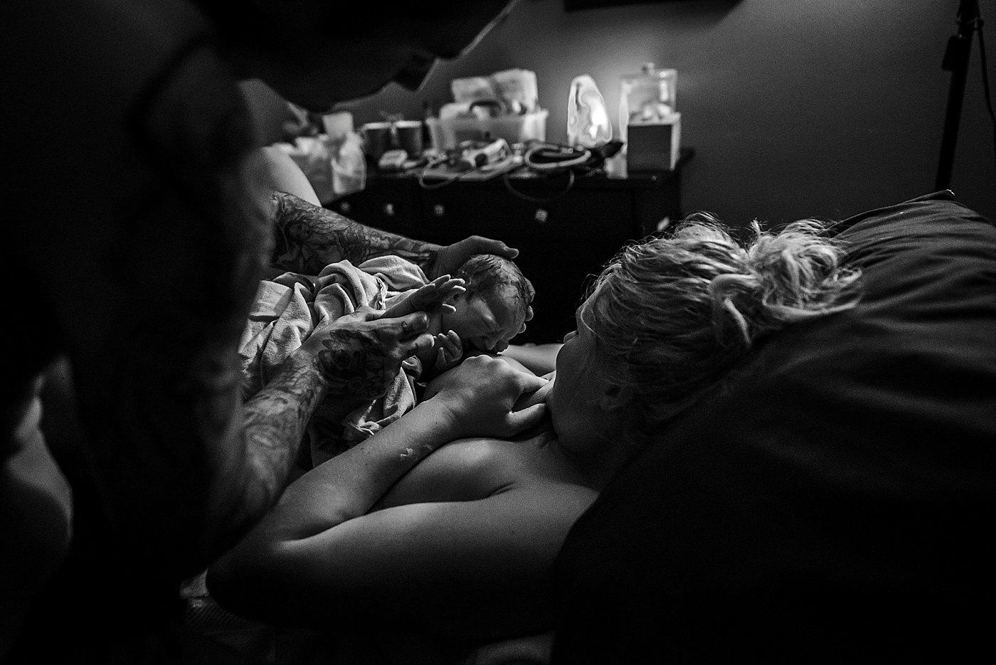 dad helps mom breastfeed newborn son redlands birth photographer