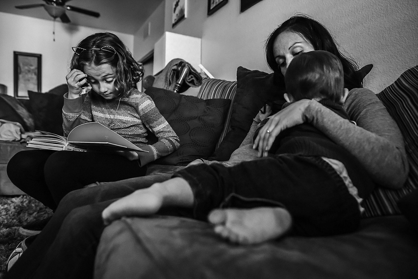 girl reading while mom nurses toddler family day in the life redlands family photography