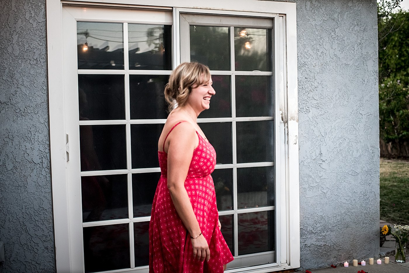 girl walks out of house smiling backyard proposal redlands family photographer