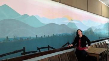 Valerie standing in front of mural