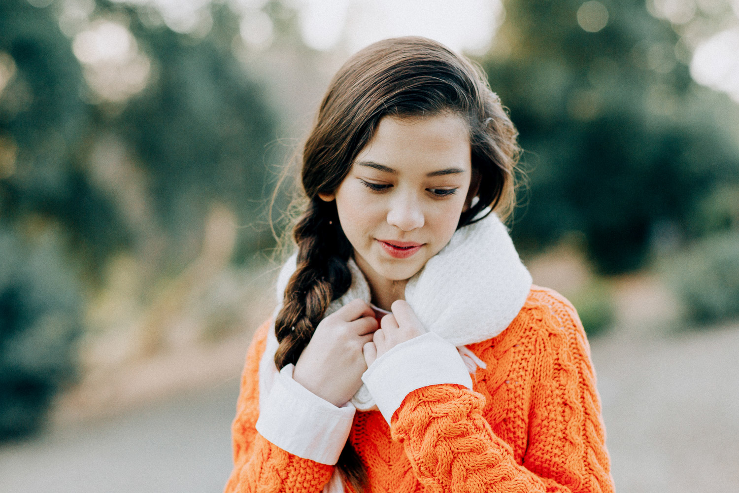 Image of an orange sweater girl looks down