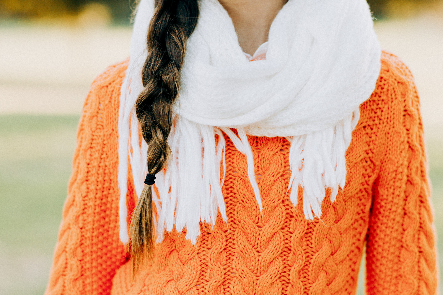 Image of the details of the orange sweater and white scraf