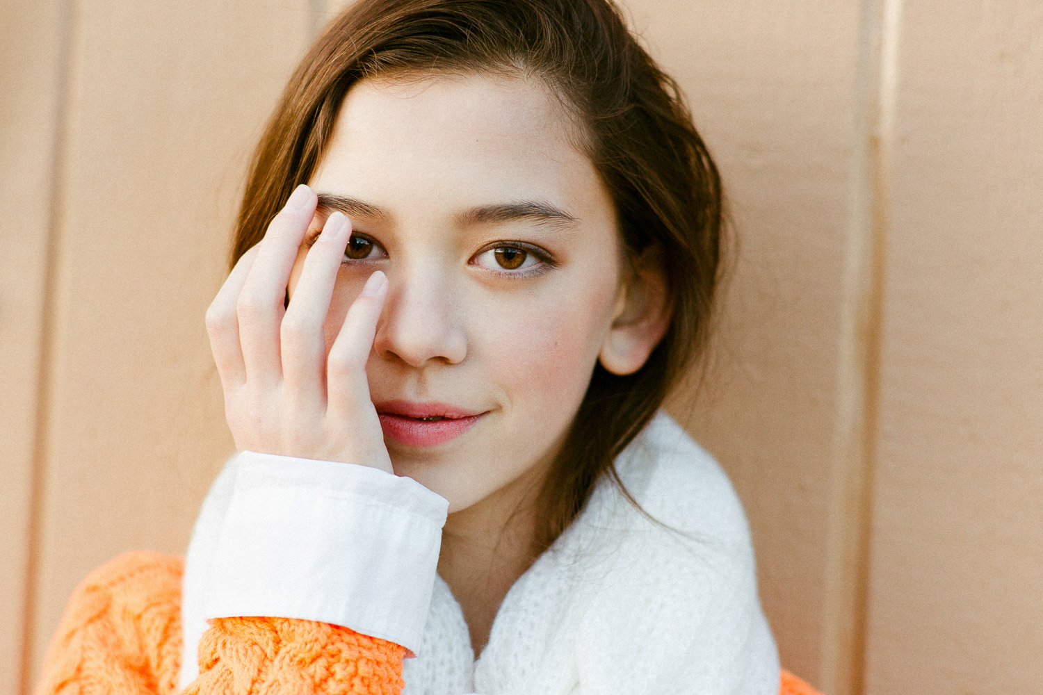 Image of an orange sweater girl covers her one eye