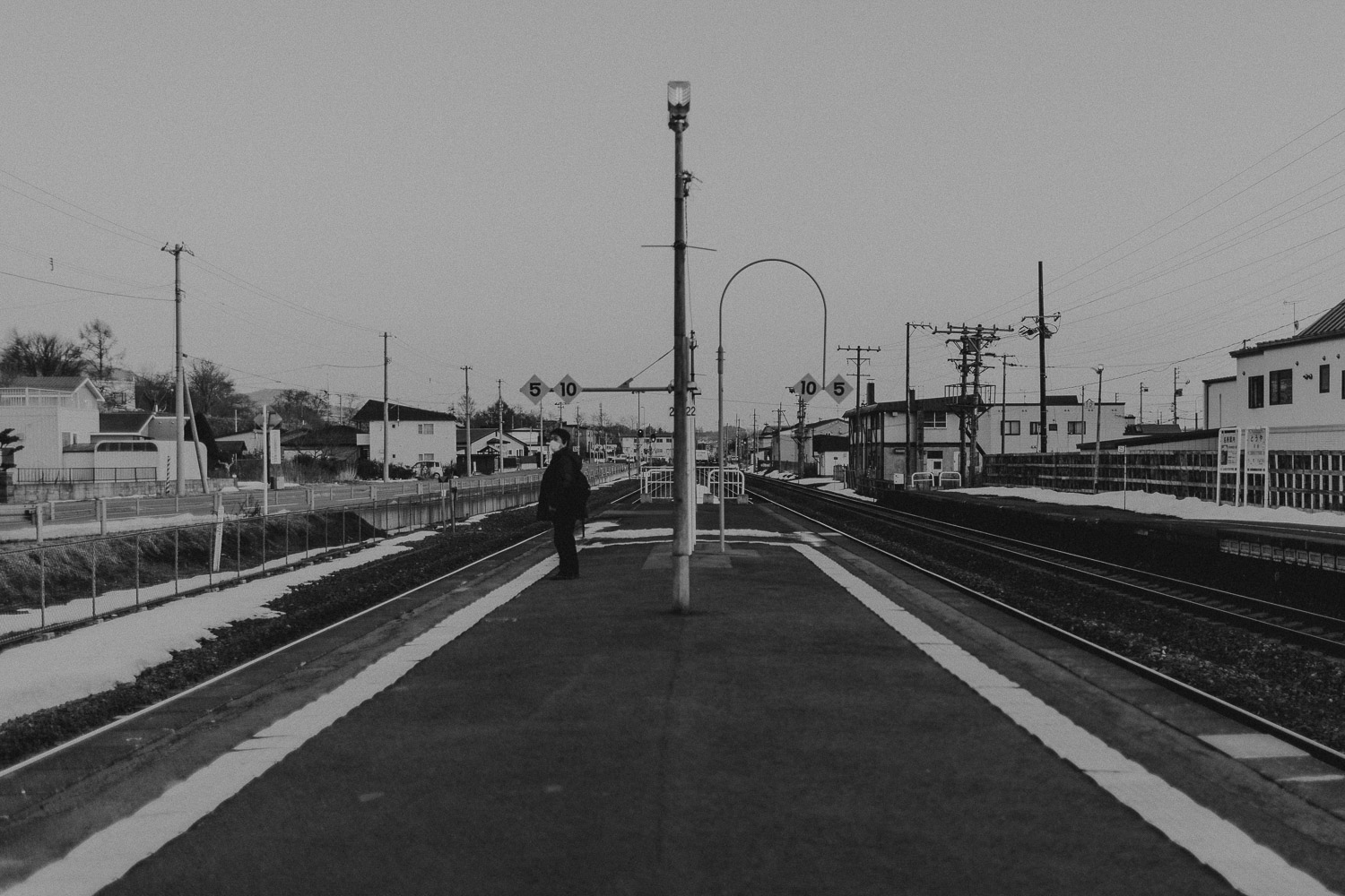 Black and White image of man waiting for train