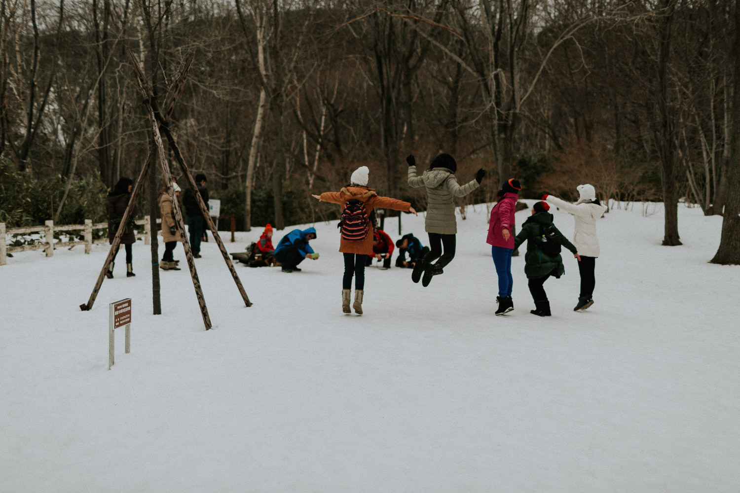 Image of group of people jumping on snow