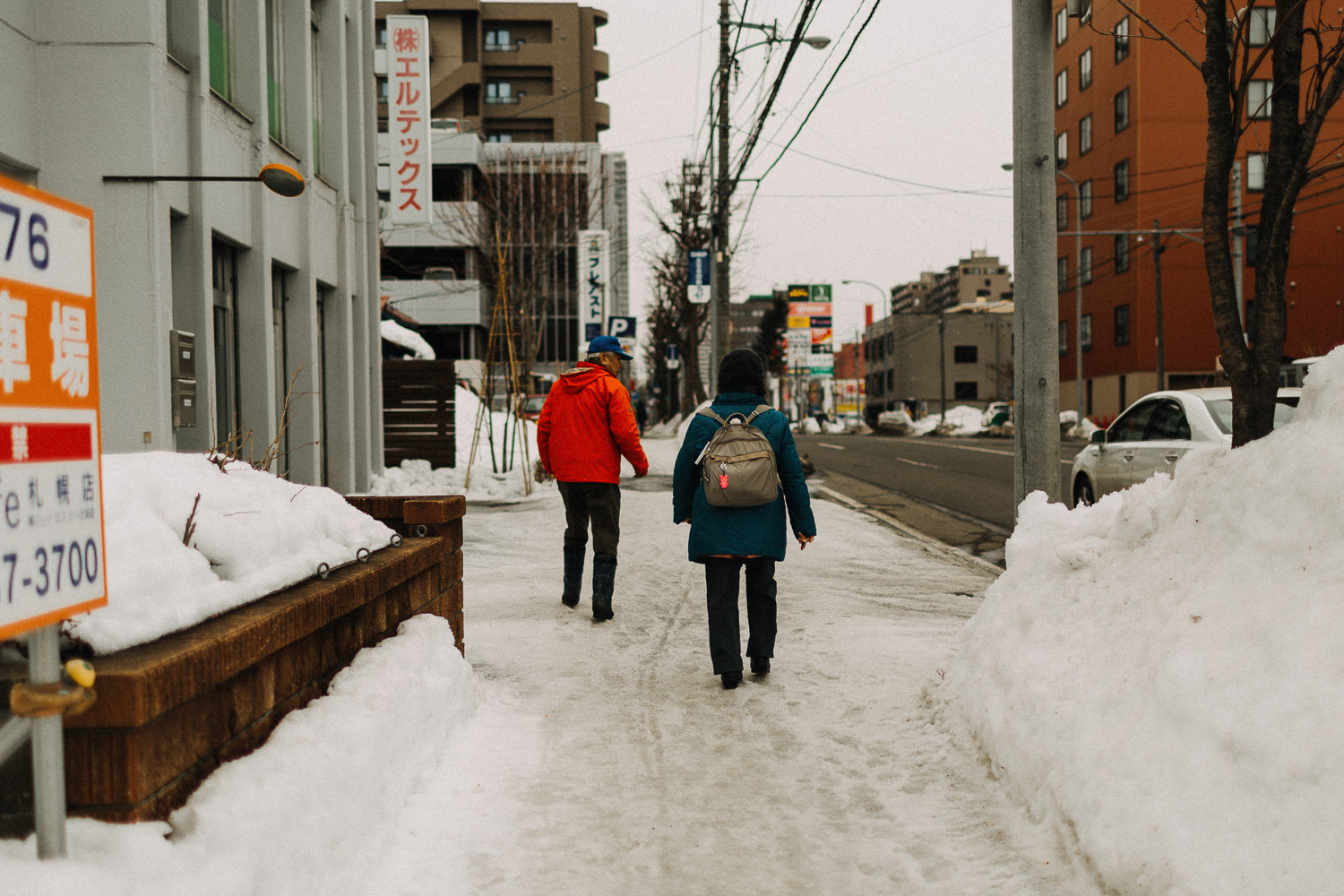 Image of two seniors walking on snow