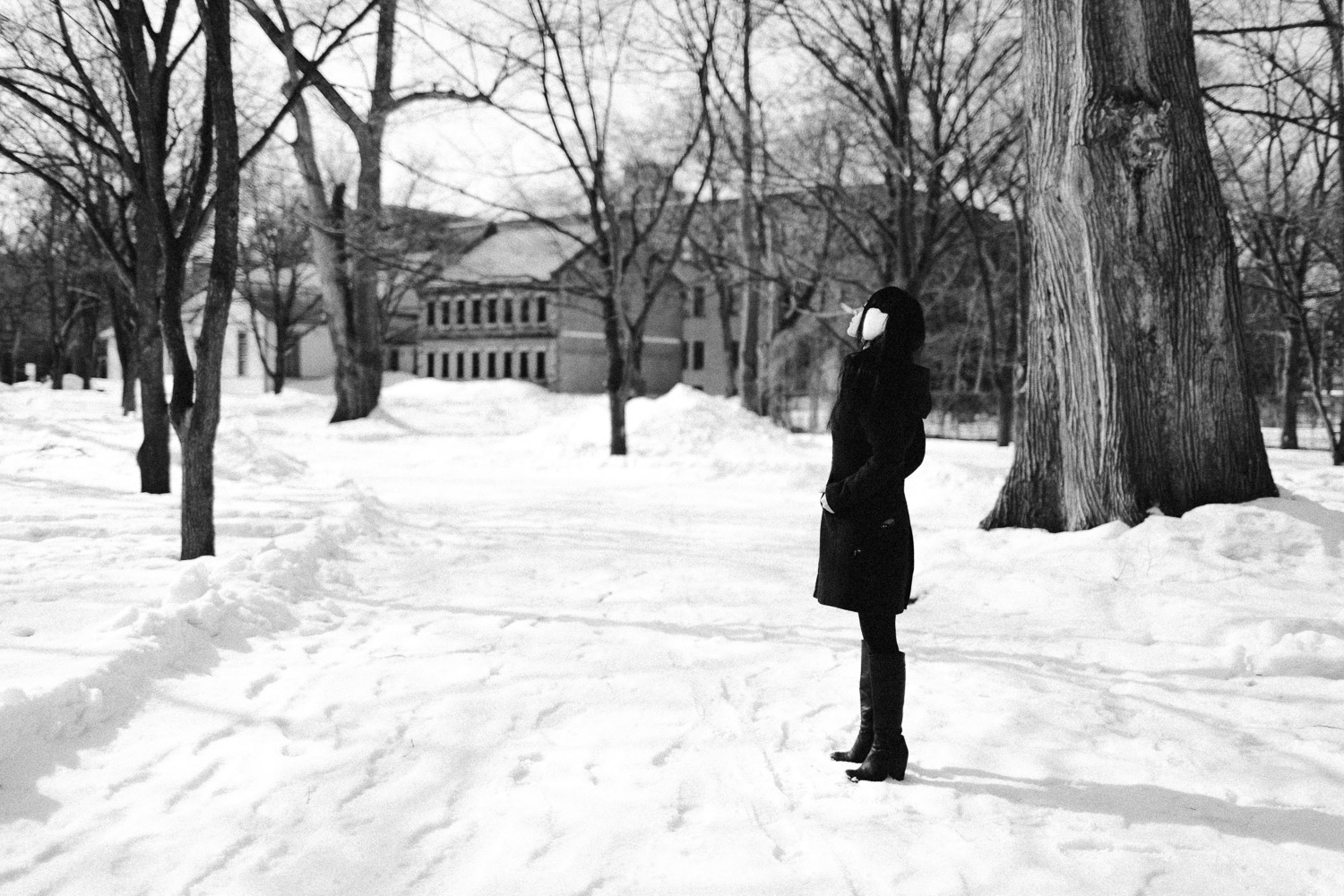 Black and White image of a girl stands in the snow