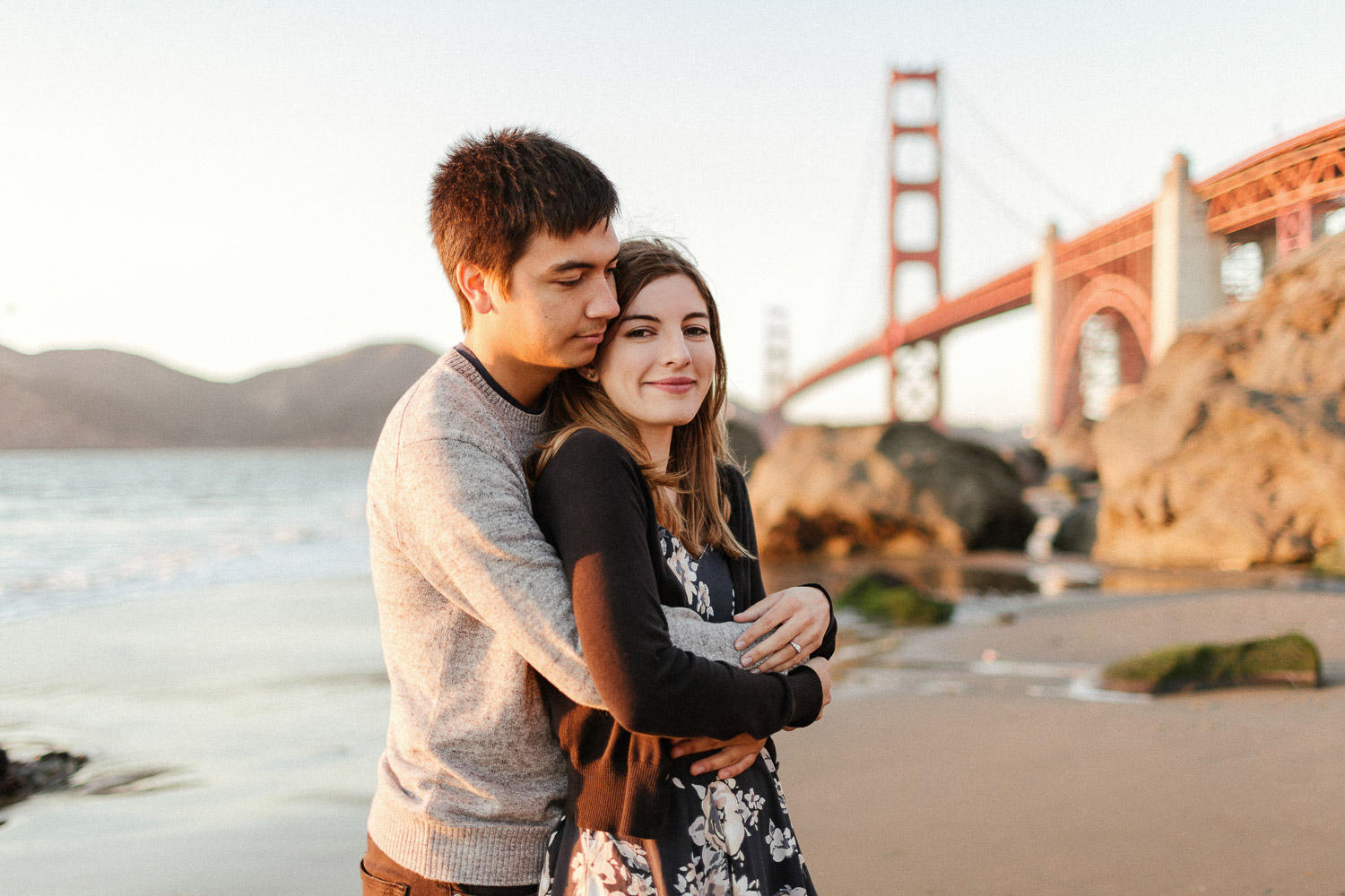 Image of couple hug each other in front of Golden Gate Bridge