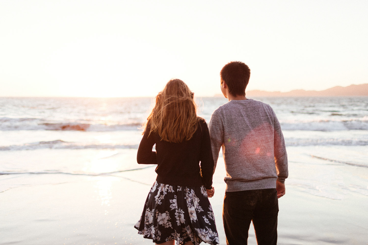 Image of couple hold hands together facing the sunset on beach