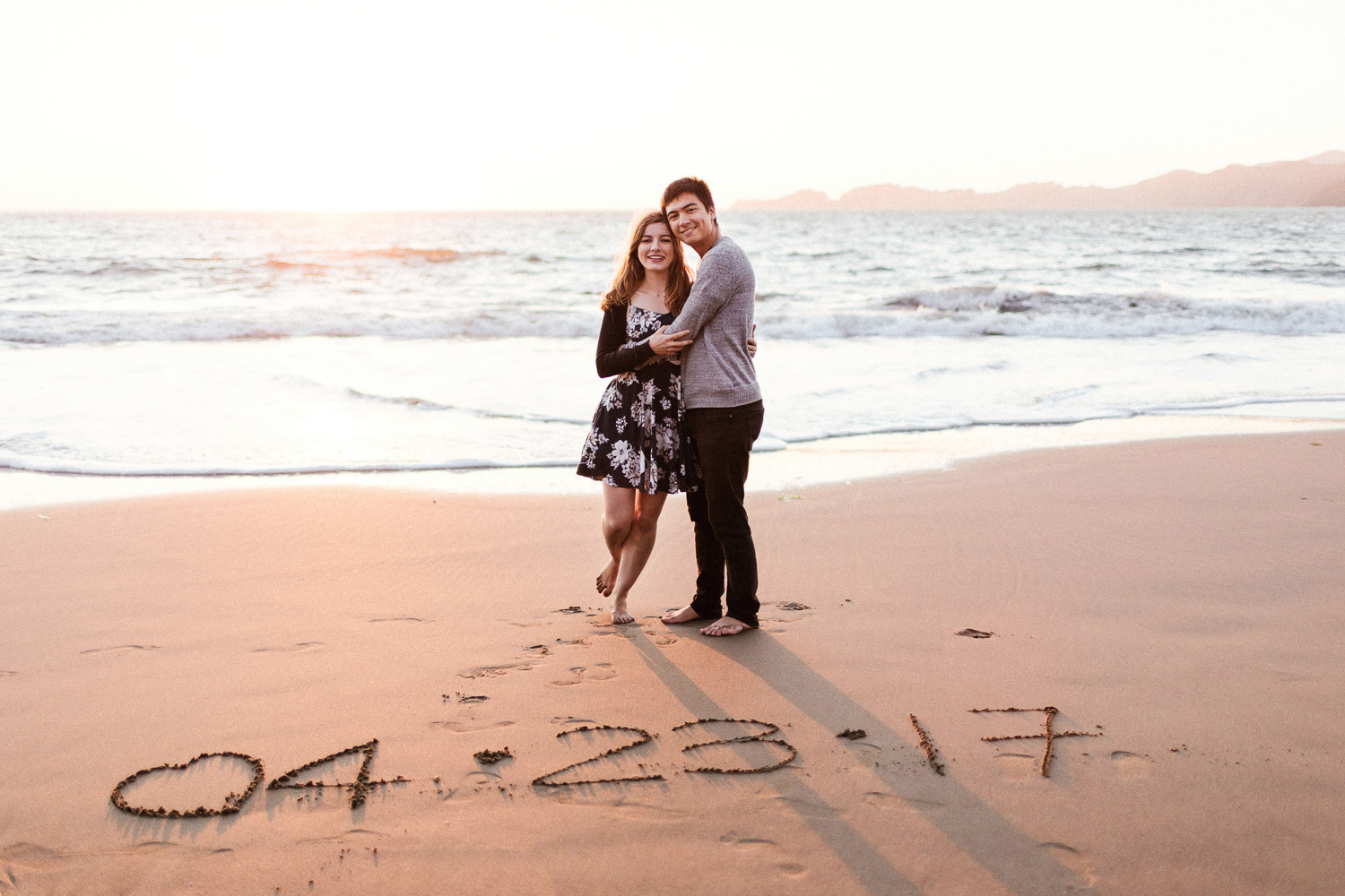 Image of couple hug each other on beach with wedding date written on sand