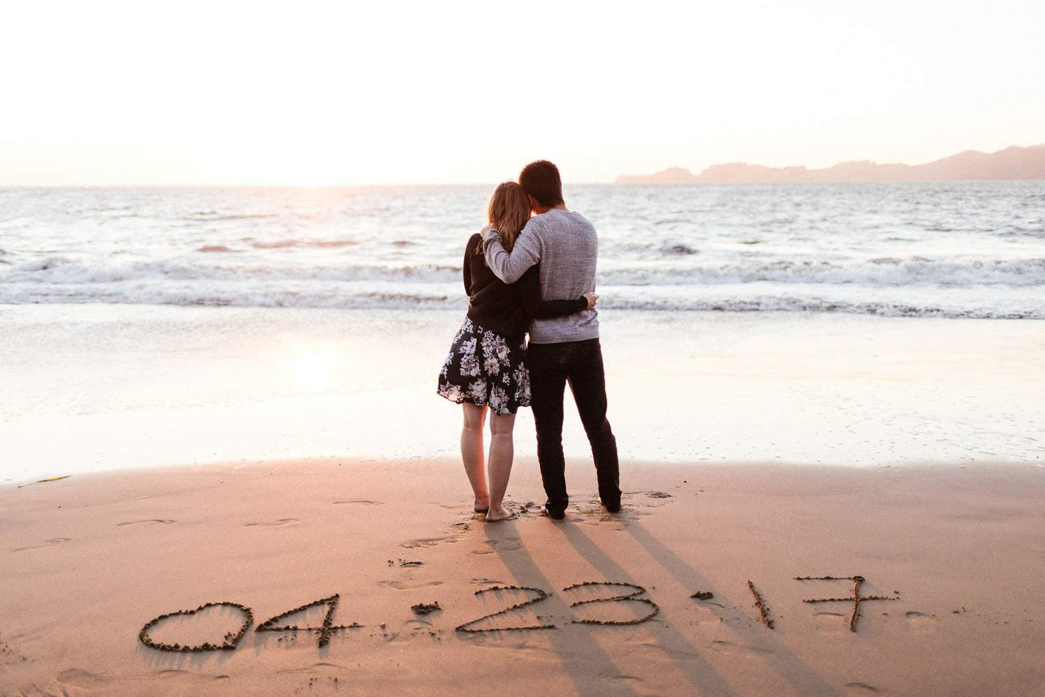 Image of couple hold each other facing the sunset with wedding date written on sand