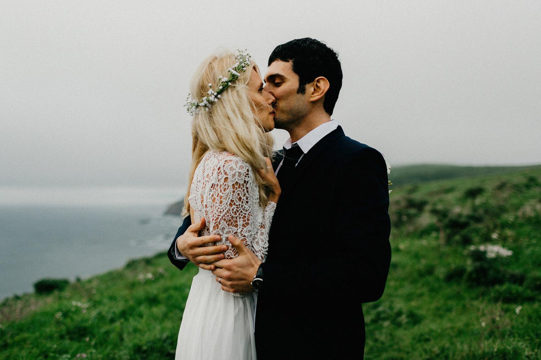 Image of groom kisses bride on her cheek