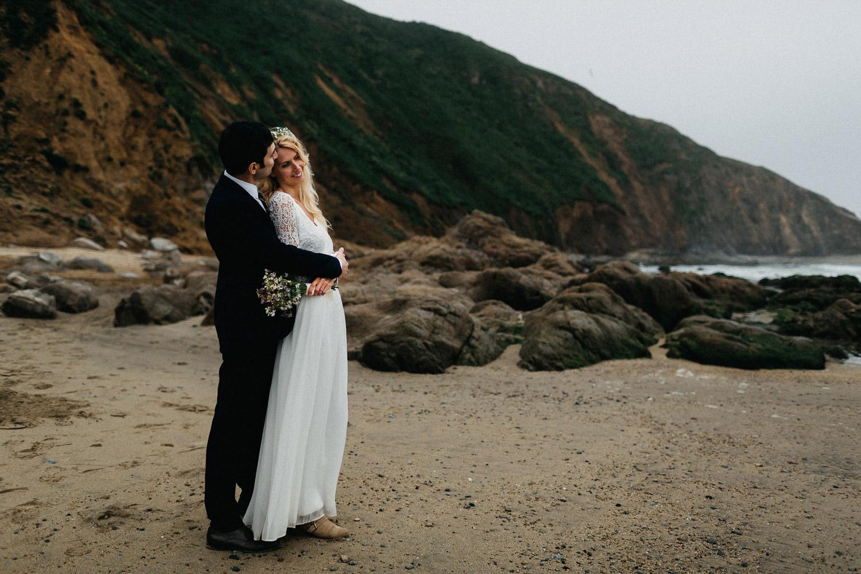Image of groom kisses bride on forhead on beach