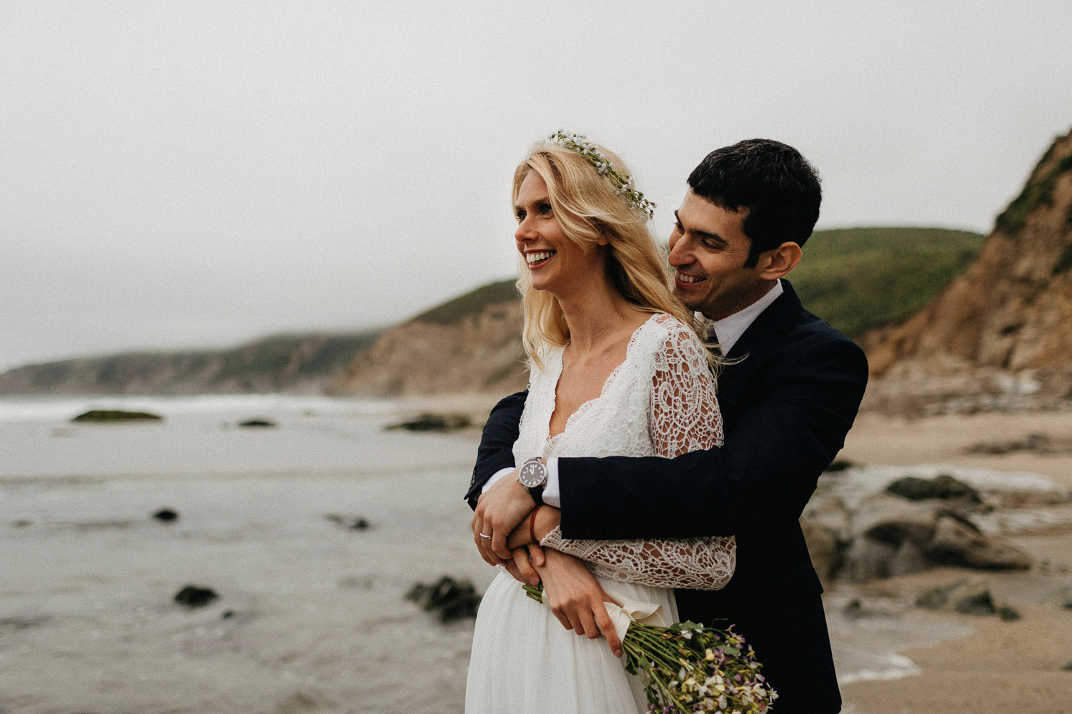 Image of groom holds bride from back