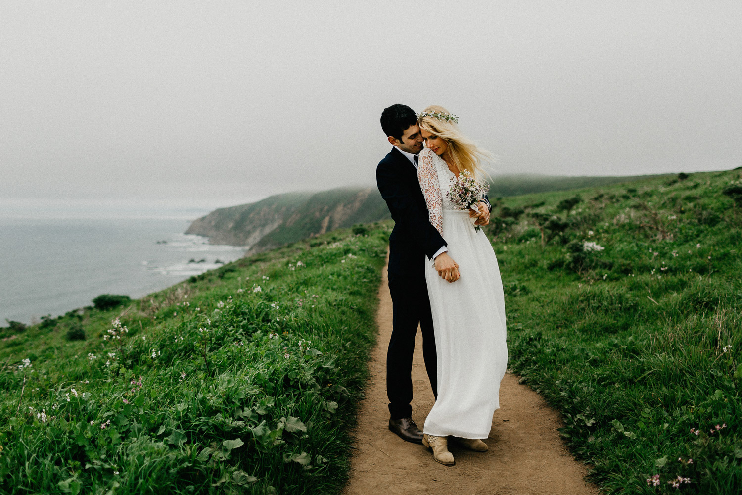 Image of groom holds bride from the back