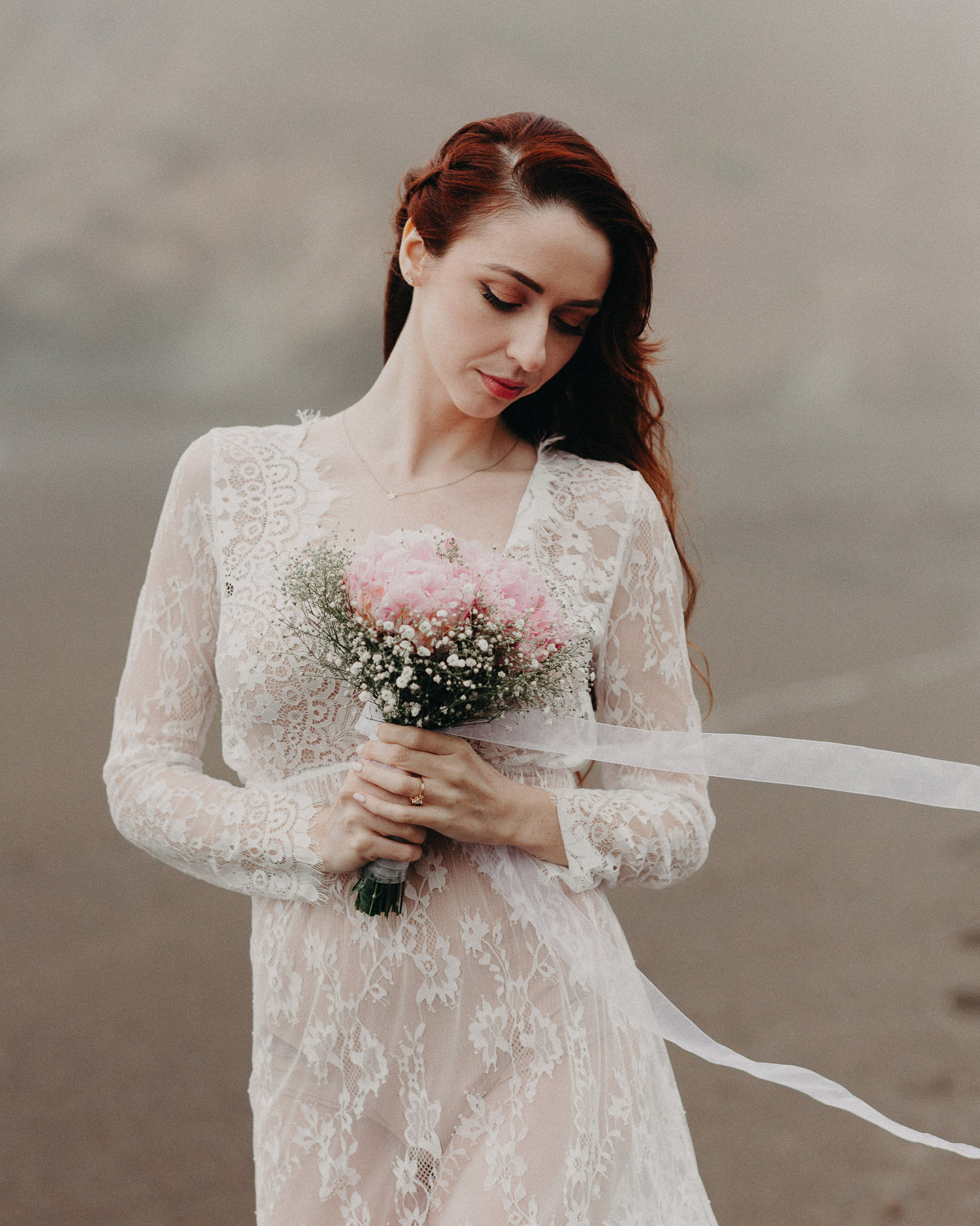 Image of red hair bride holds pink flower bouquet