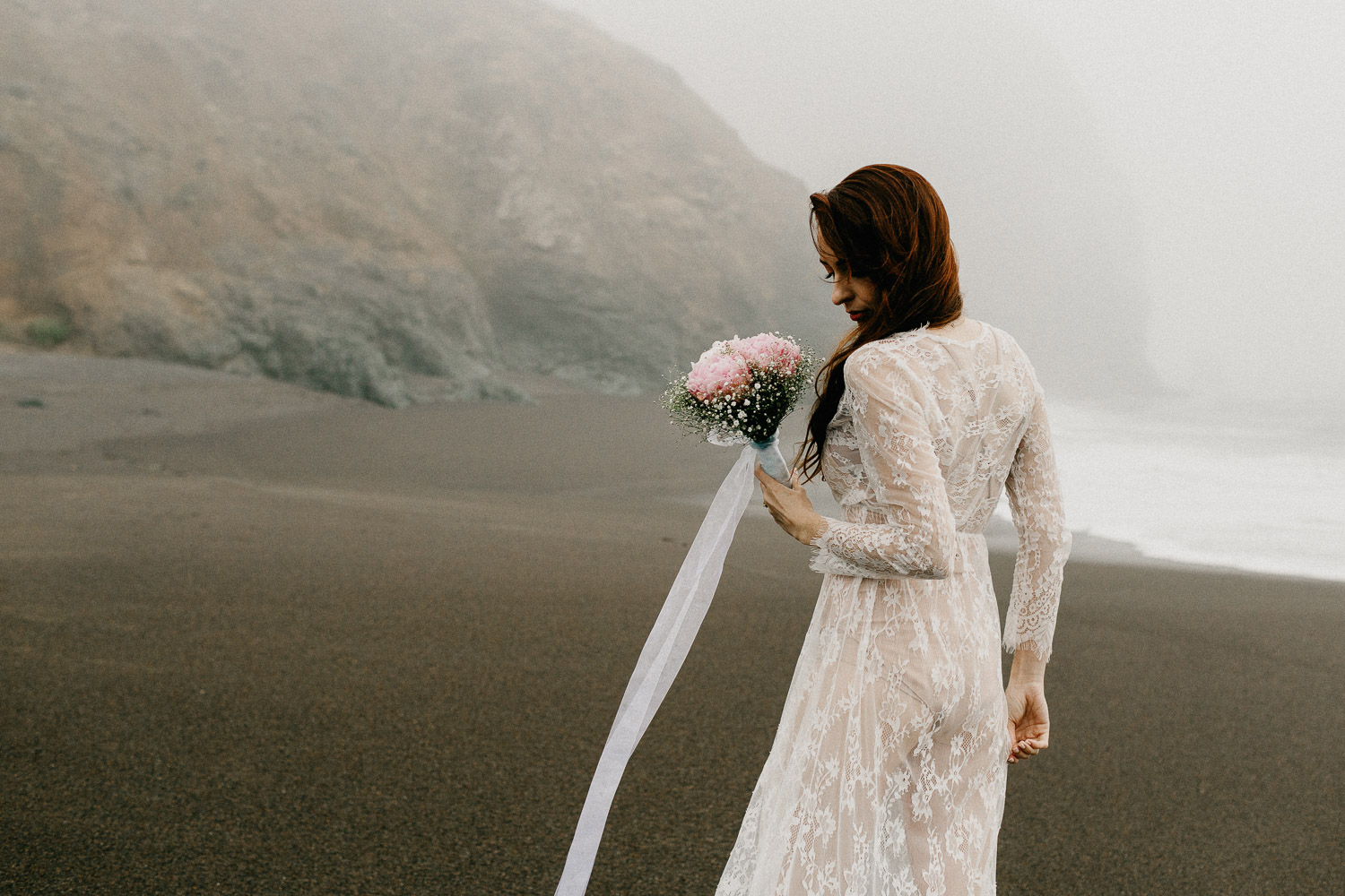 Image of red hair bride holds pink bouquet back facing the camera