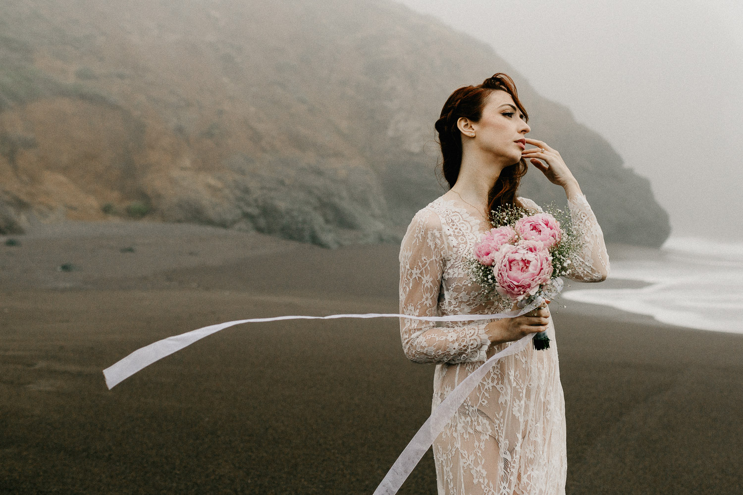 Image of red hair bride holds pink bouquet looks at ocean on beach