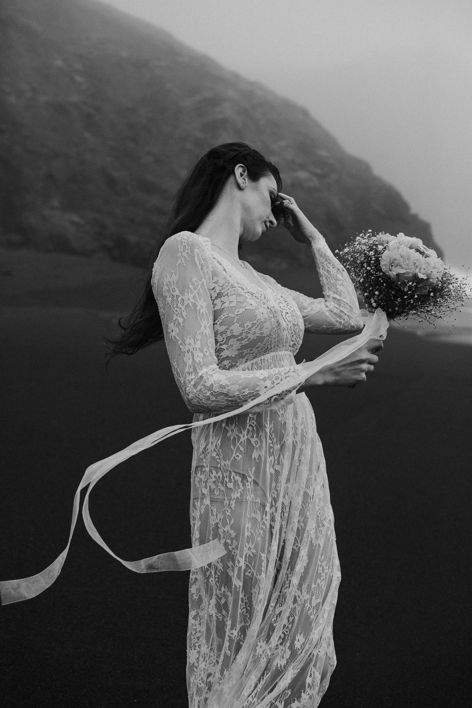 Black and White image of bride holds bouquet on beach