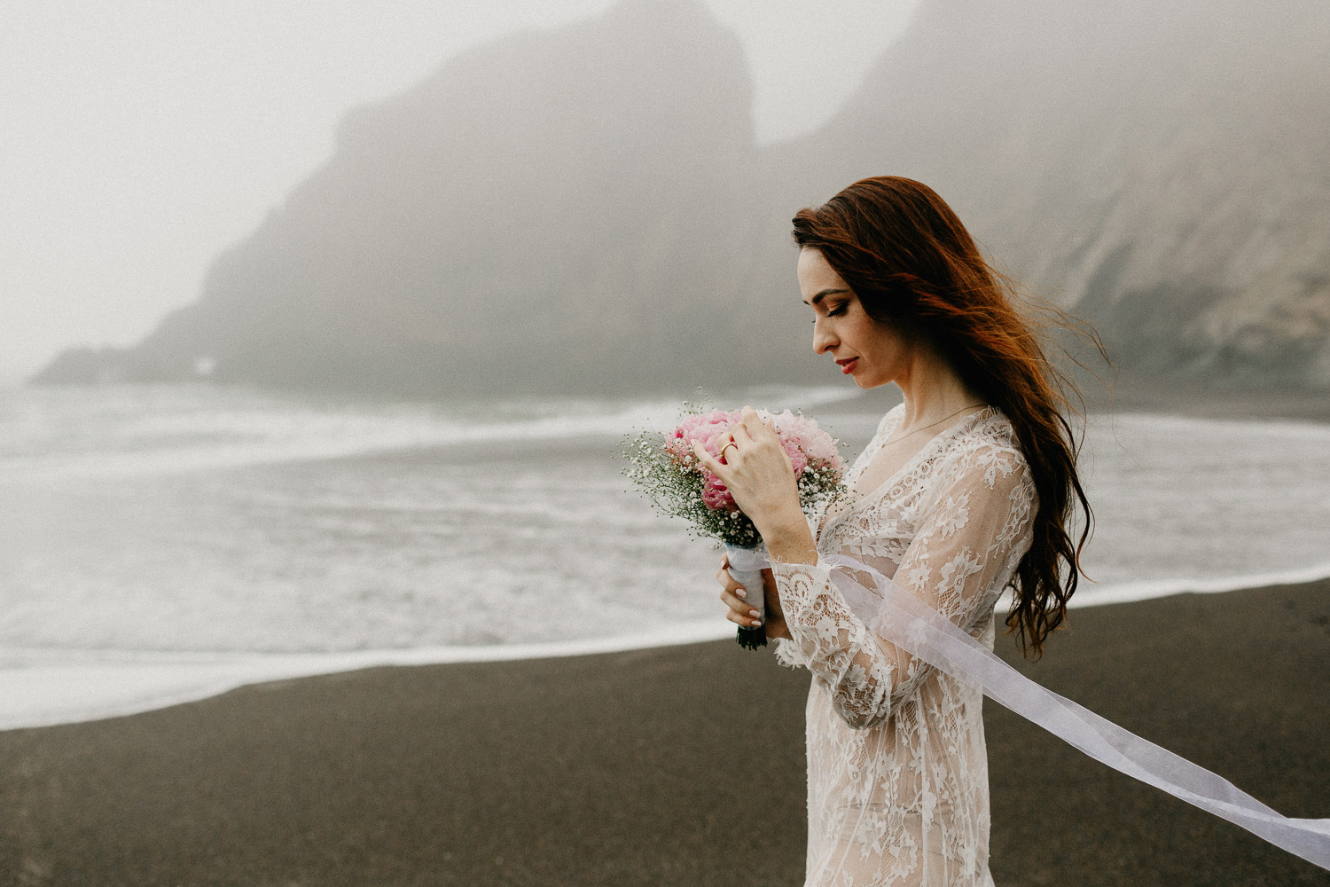 Image of red hair bride plays with pink bouquet on beach