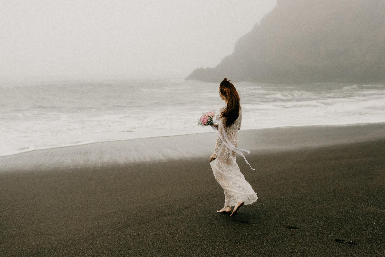 Image of bride holds bouquet walks towards ocean