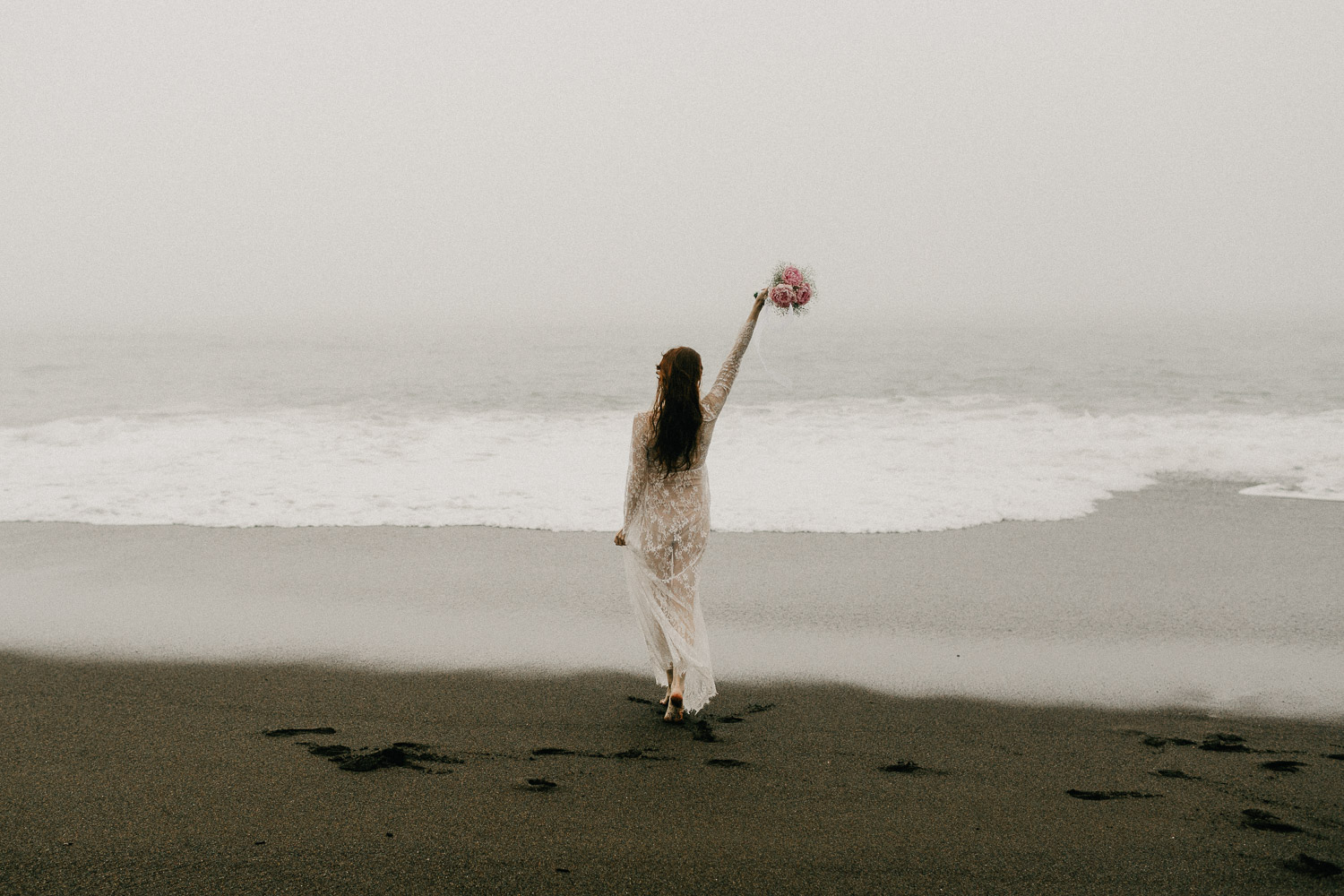 Image of bride raises her arm in front of ocean on beach