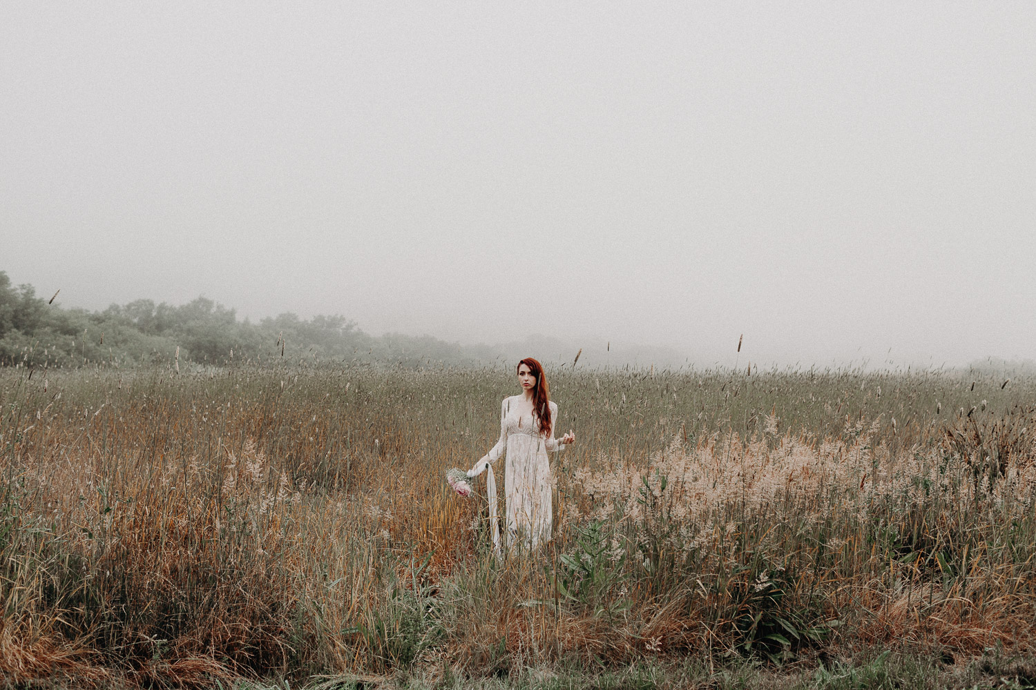 Image of red hair bride stands in tall grass in front the mountain