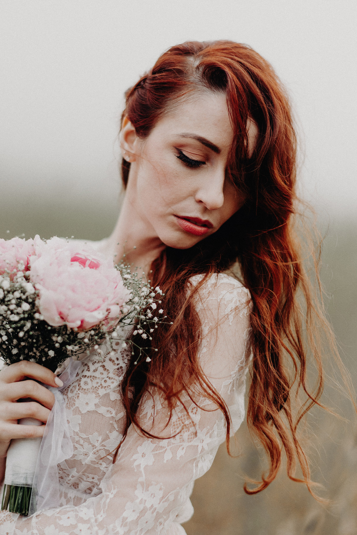 Image of red hair bride holds pink bouquet and looks down