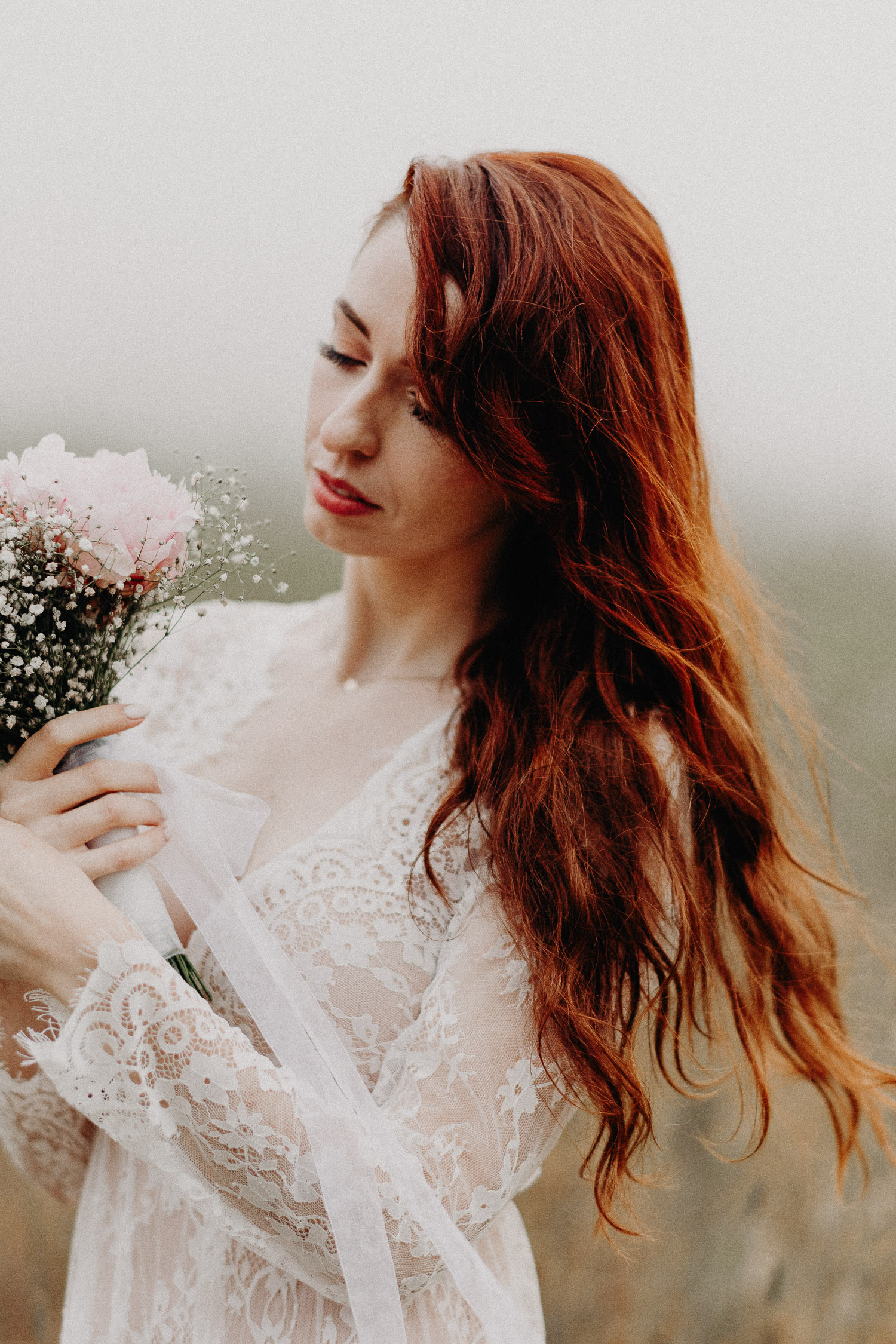 Image of red hair bride looks at the pink bouquet