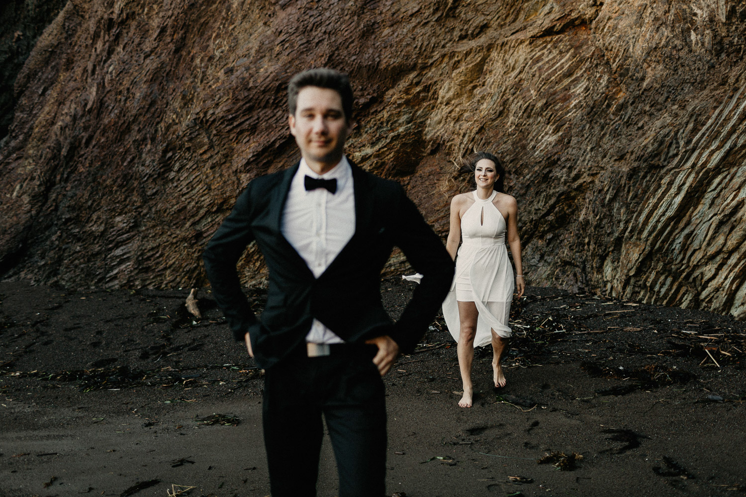 Image of groom stands in front of bride on beach