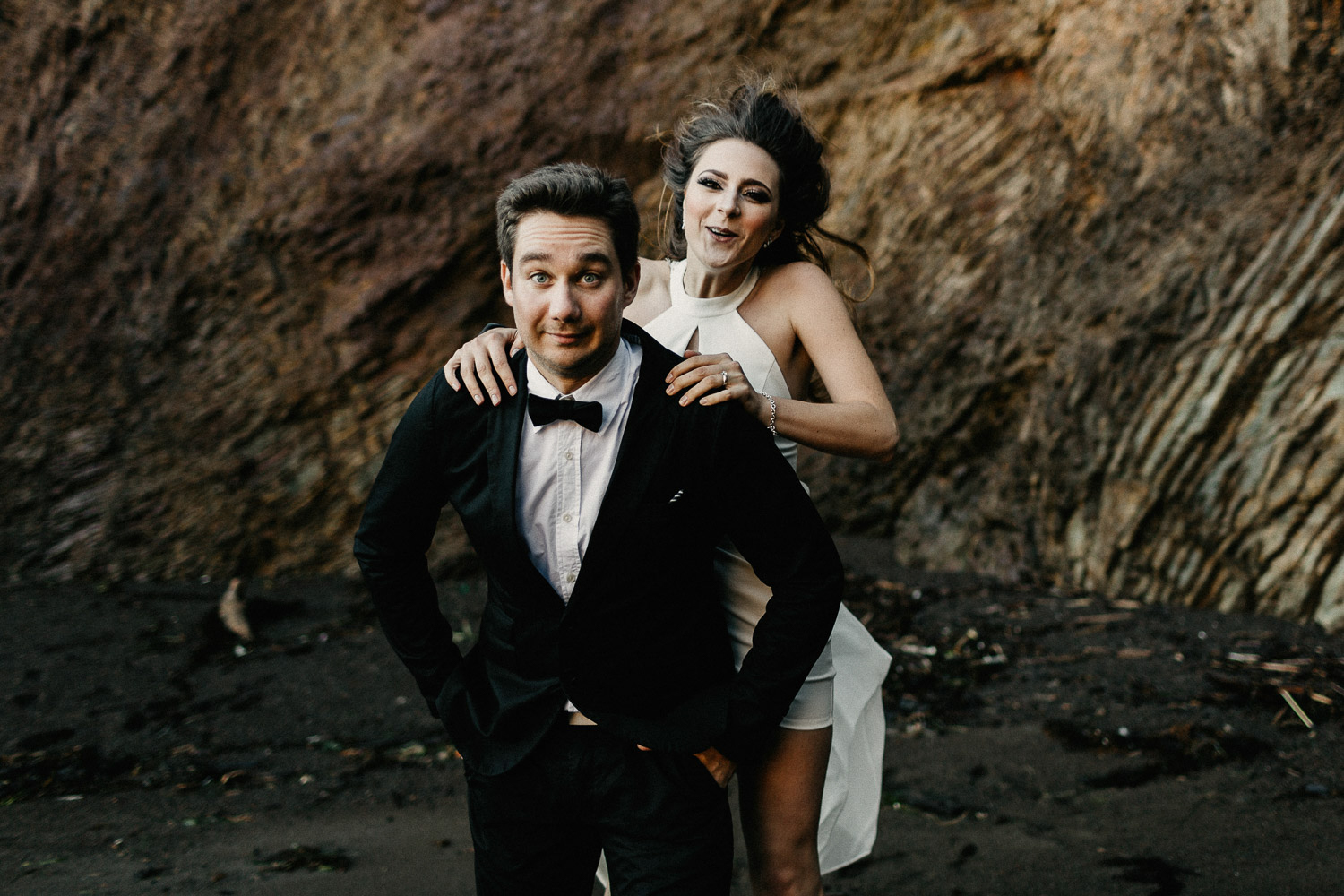 Image of bride jumps on the back of groom on beach