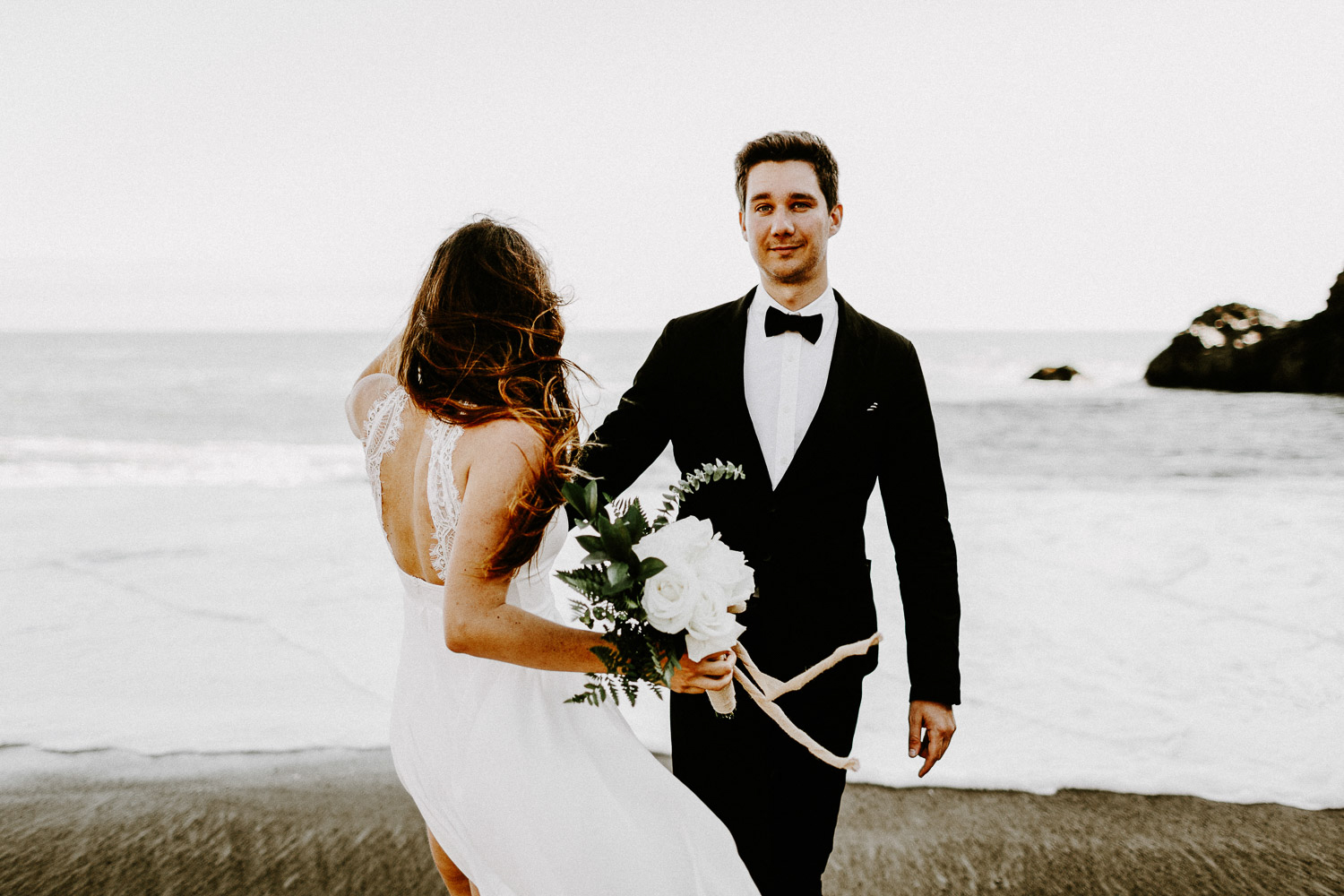 Image of bride faces the ocean while groom faces the camera