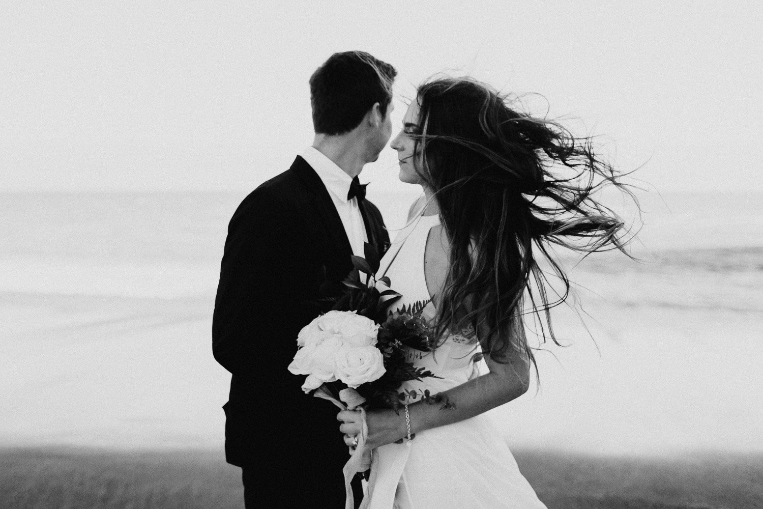 Black and White image of groom and bride stand together on beach