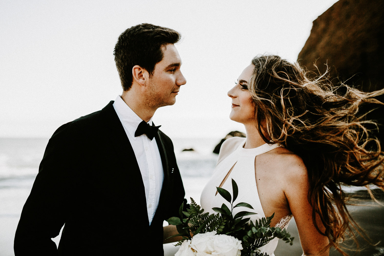 Image of groom and bride look at each other on beach