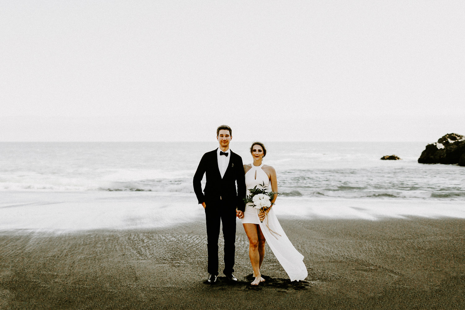 Image of groom stand together with bride on beach