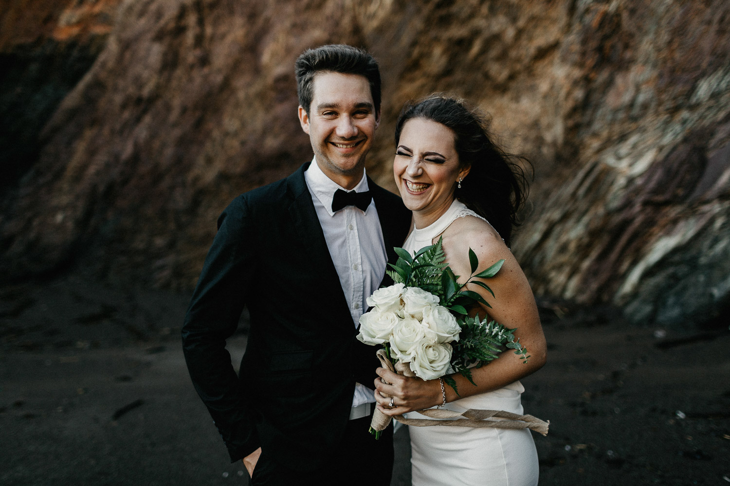 Image of groom and bride laugh together on beach