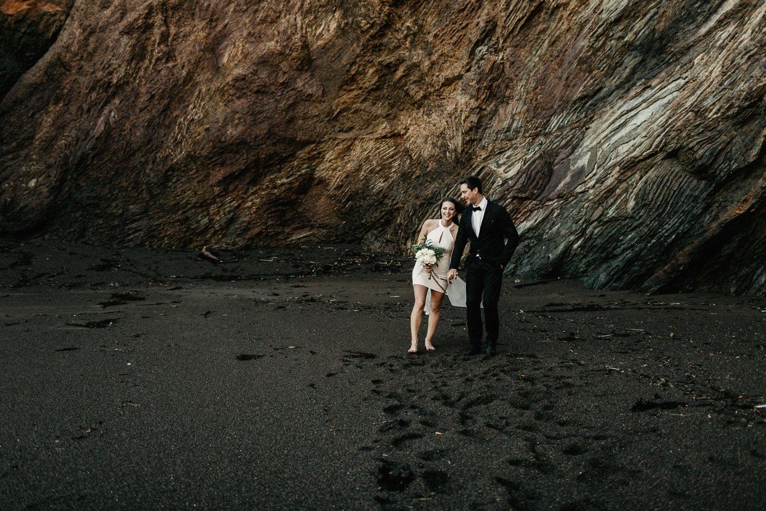 Image of groom and bride walk together on beach