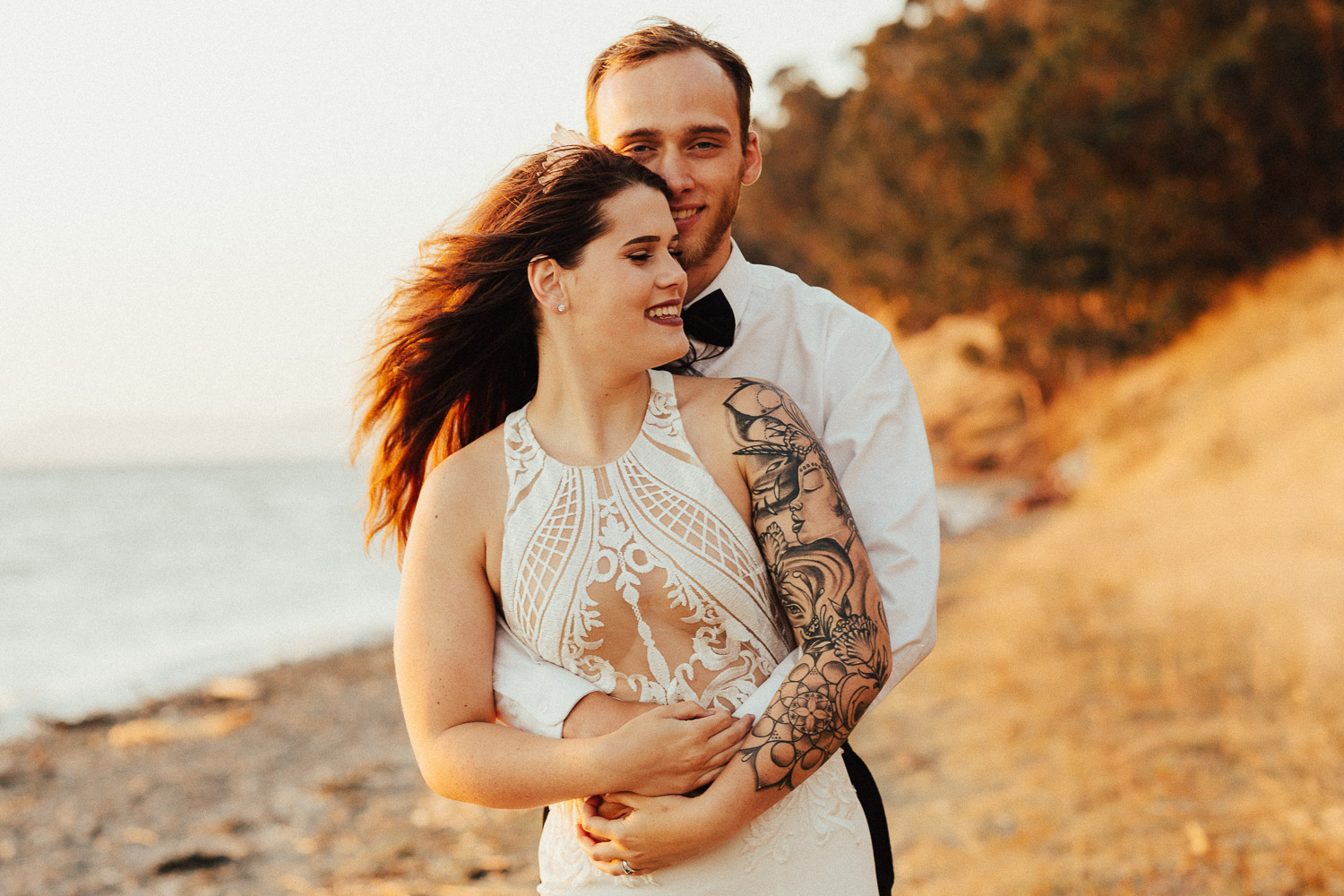 Image of groom holds bride from the back in sunset next to water